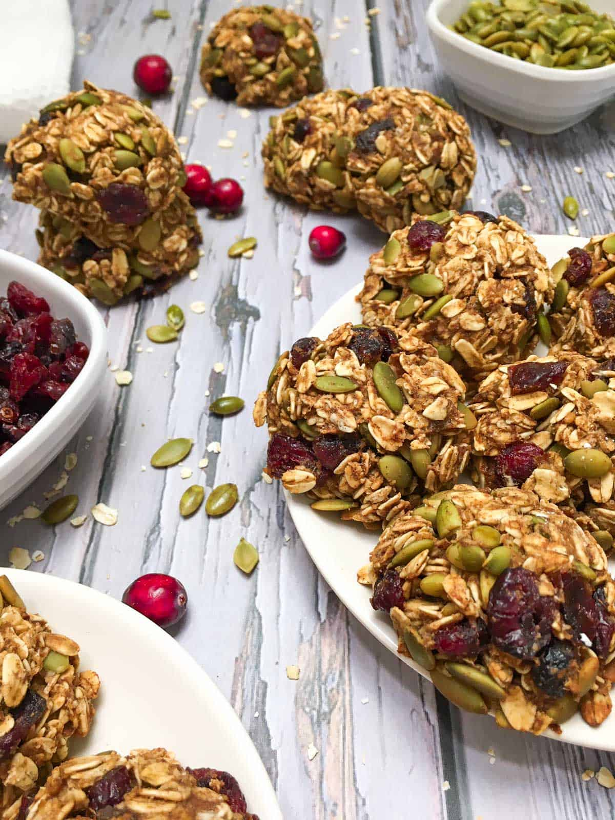 Cranberry oatmeal cookies on white plate with bowls of cranberries and pumpkin seeds around it.