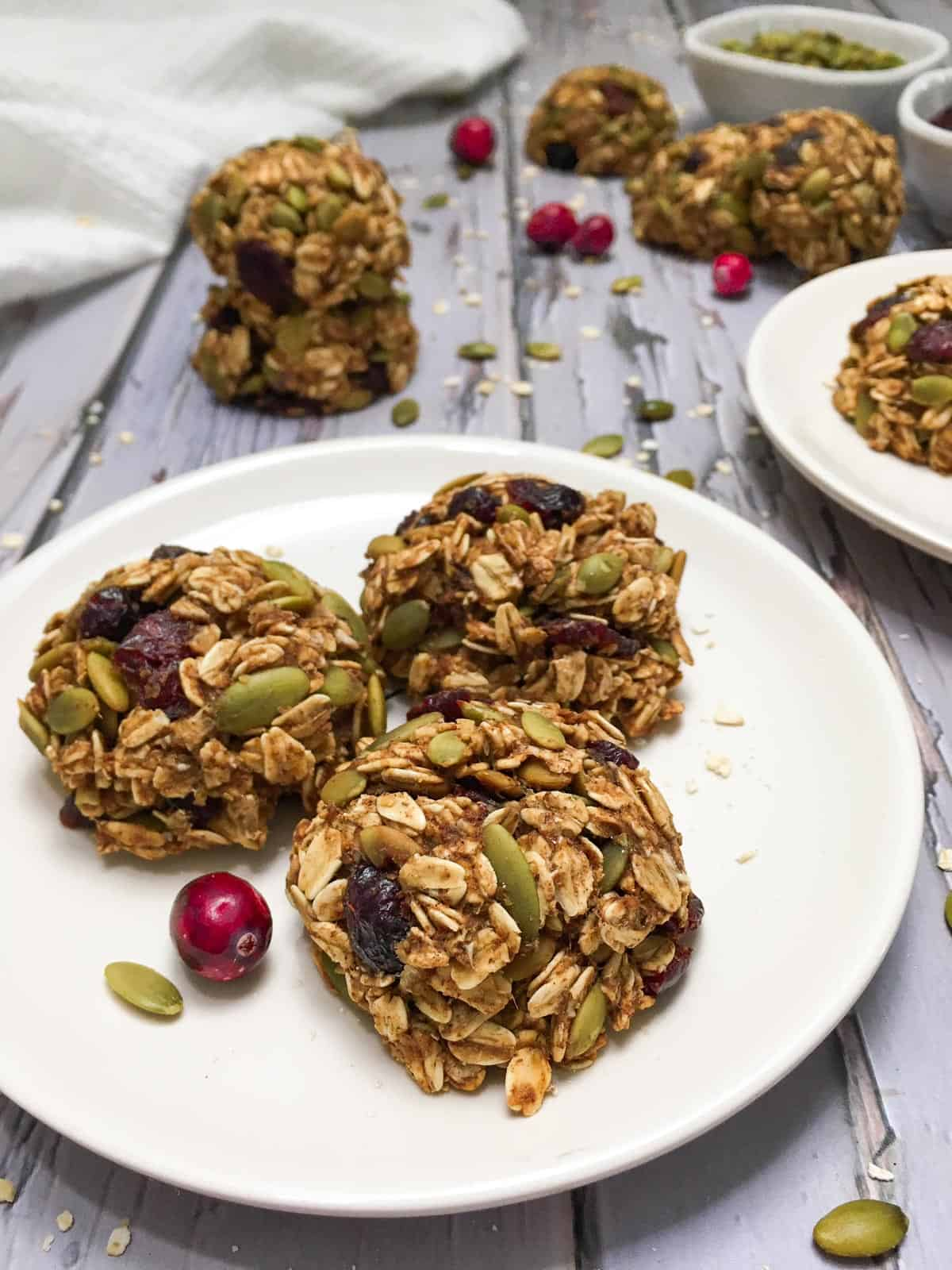 Three cranberry cookies on white plate with more cookies scattered in the background.