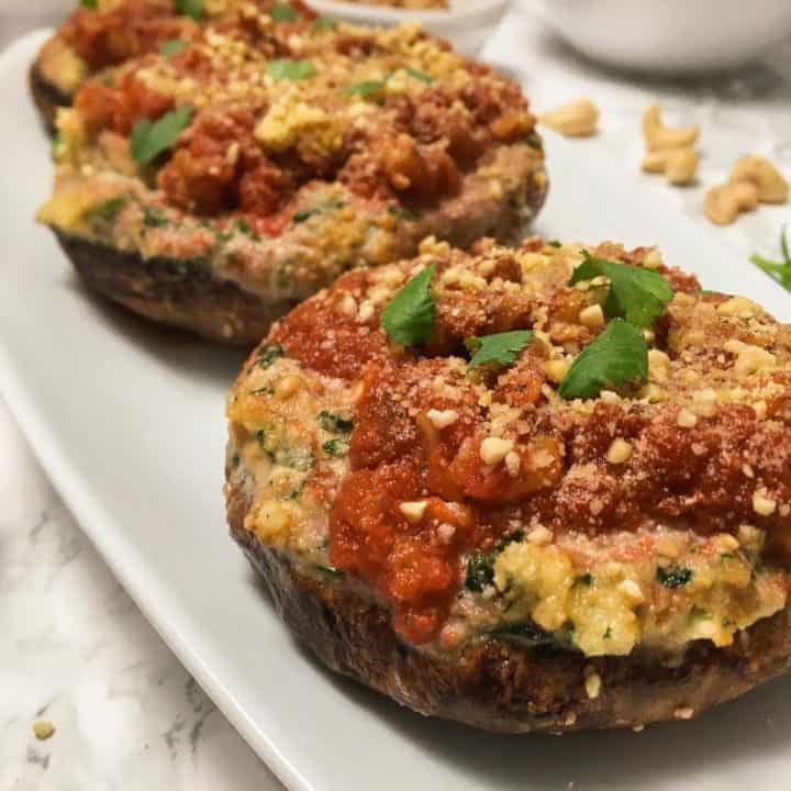 lasagna stuffed portobello mushrooms on white serving dish.