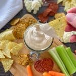 vegan walnut cheese sauce in glass container with hand holding dipped chip above it.