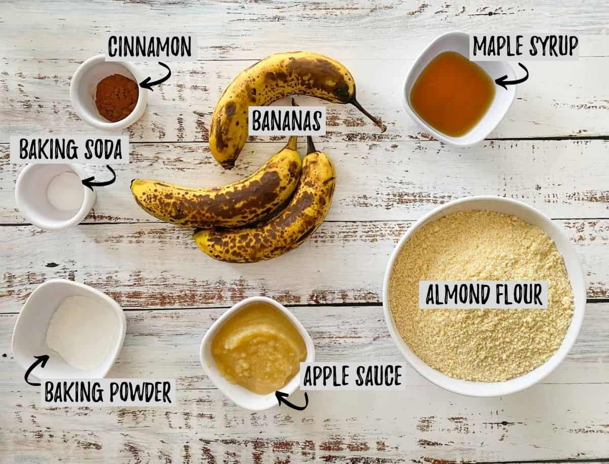 Bowl of almond flour, ripe bananas, and small prep bowls on white deck.