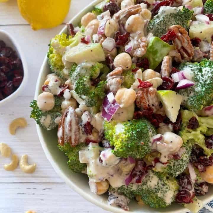 Large salad in white serving bowl with lemons, pecans, and cranberries around it.