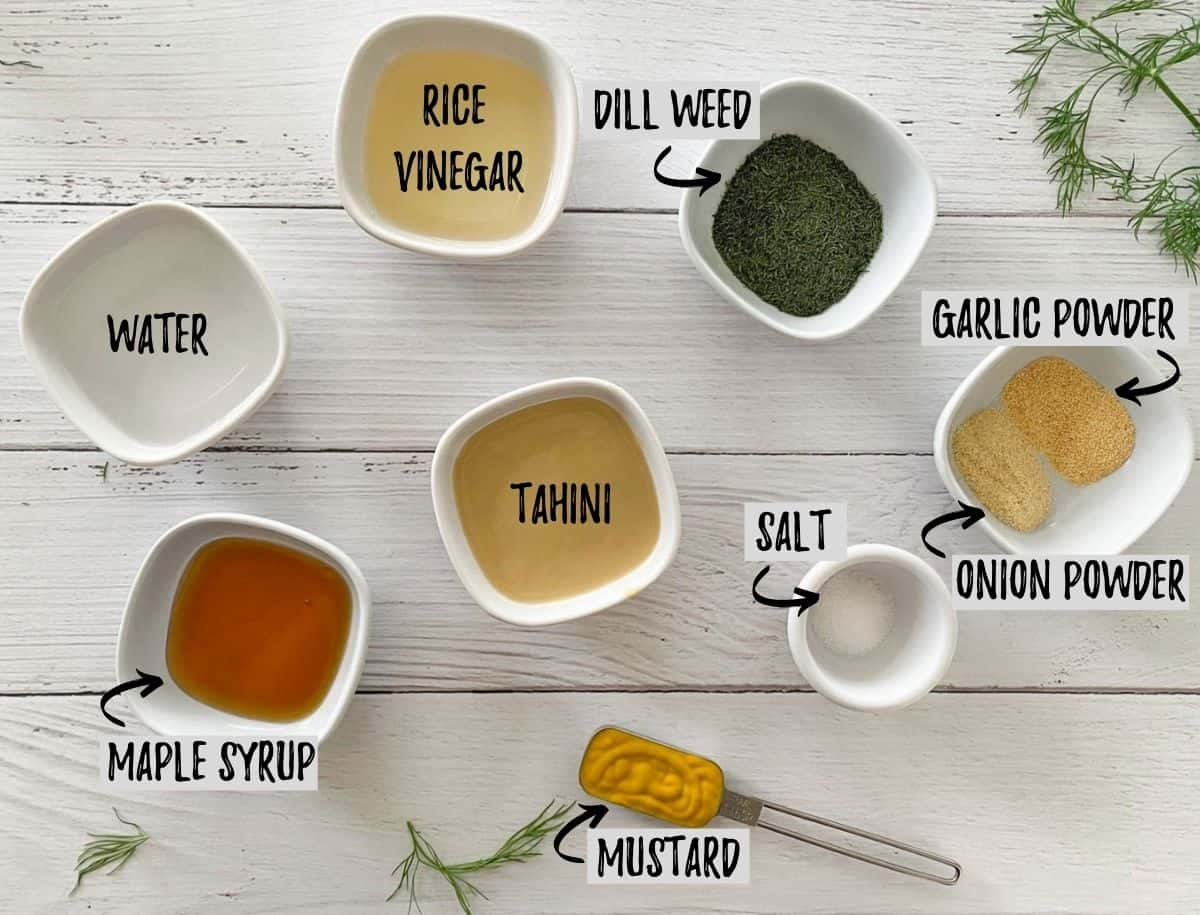 Ingredients to make salad dressing in small bowls on white deck.