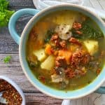 Bowl of soup with potatoes, kale, carrots and vegan bacon.
