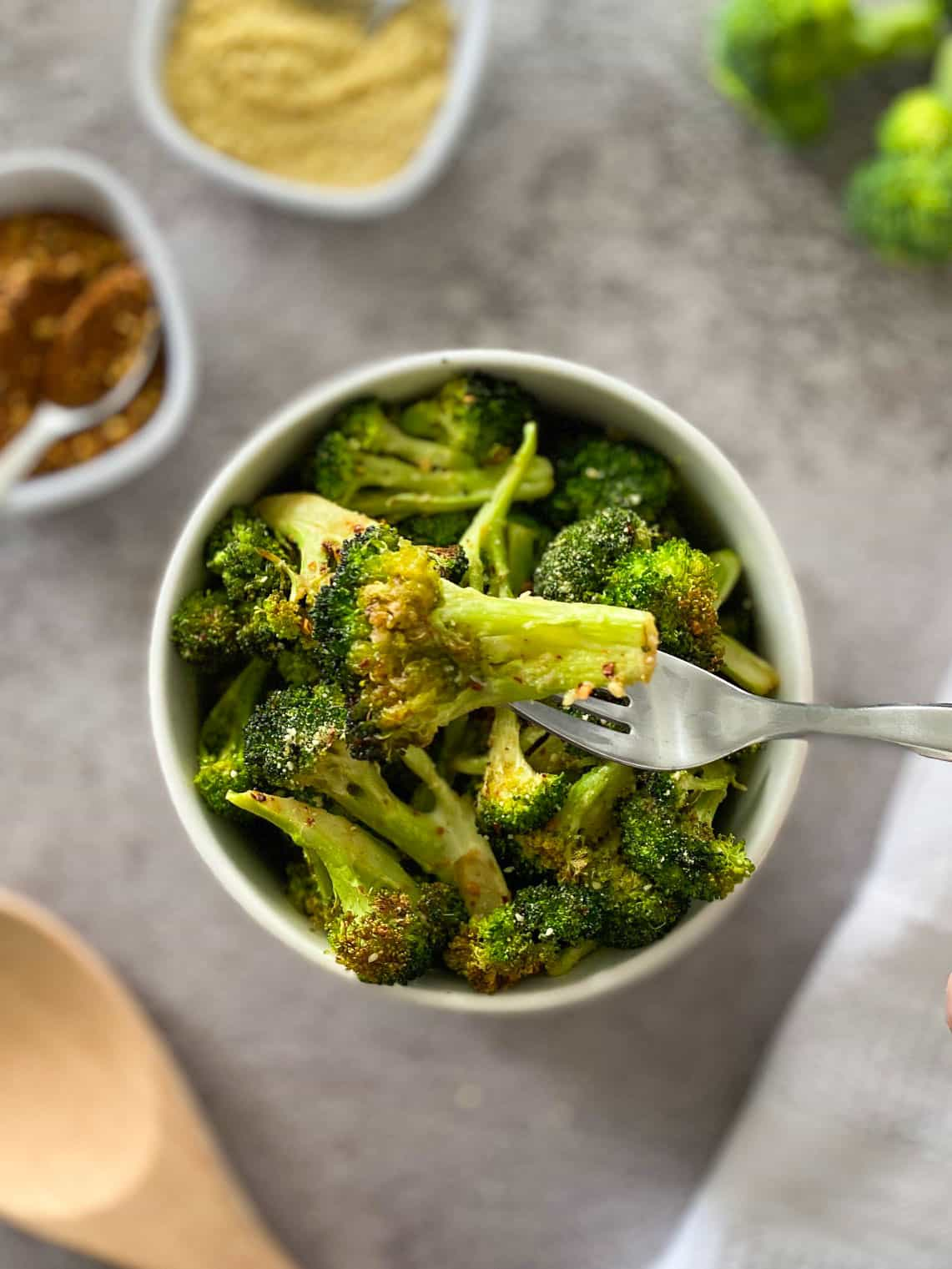 Fork holding up a broccoli floret over a bowl of more broccoli.