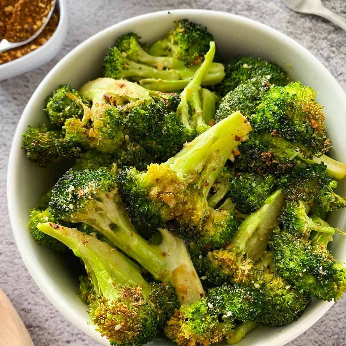 close up of bowl full of air fried broccoli