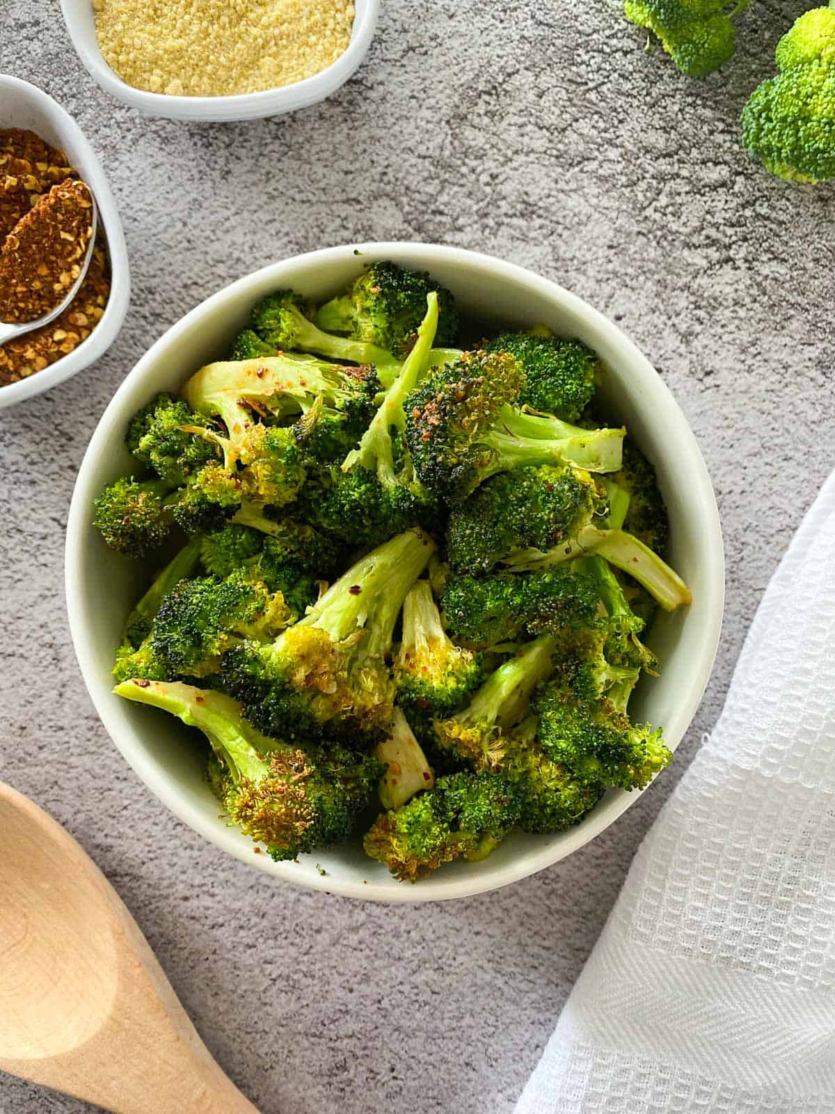 Air fried broccoli in white bowl with white dish towel beside it.