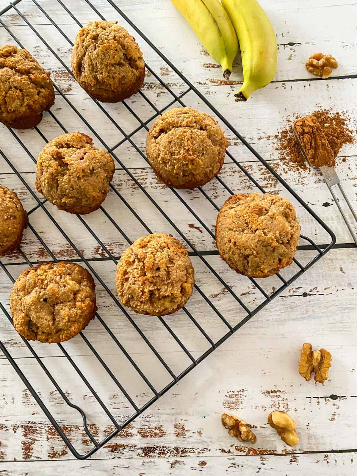 Muffins on cooling rack with bananas, walnuts and cinnamon scattered around.