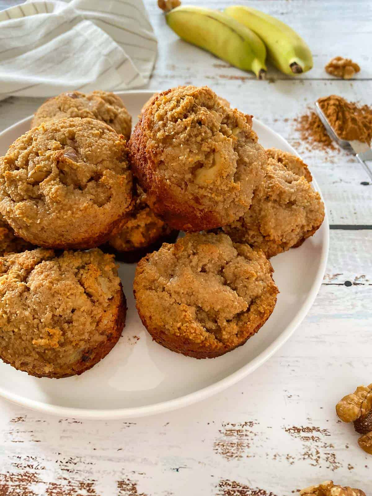 Banana muffins stacked on white plate.