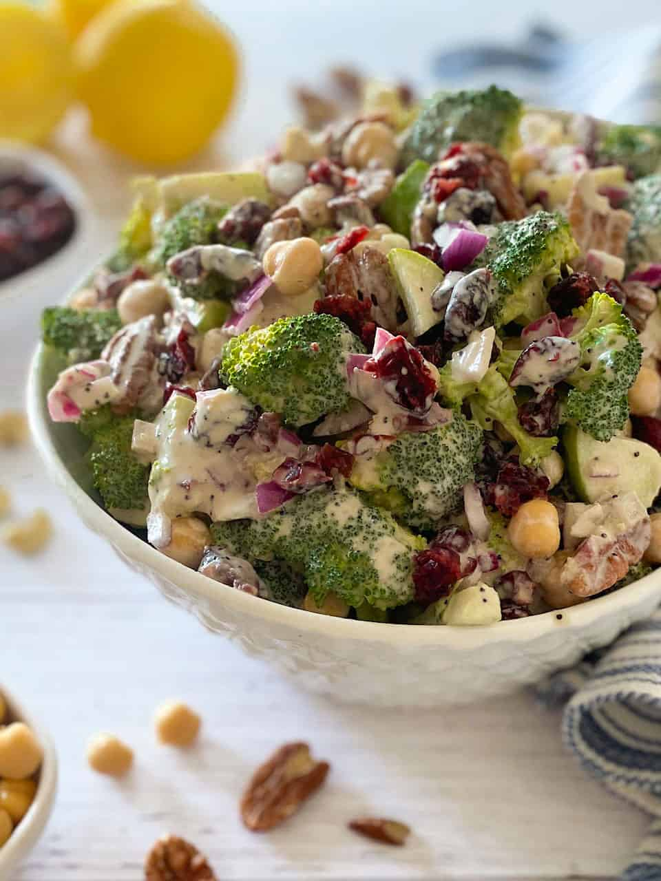 Side view of cranberry broccoli salad in white serving bowl with lemons in the background.