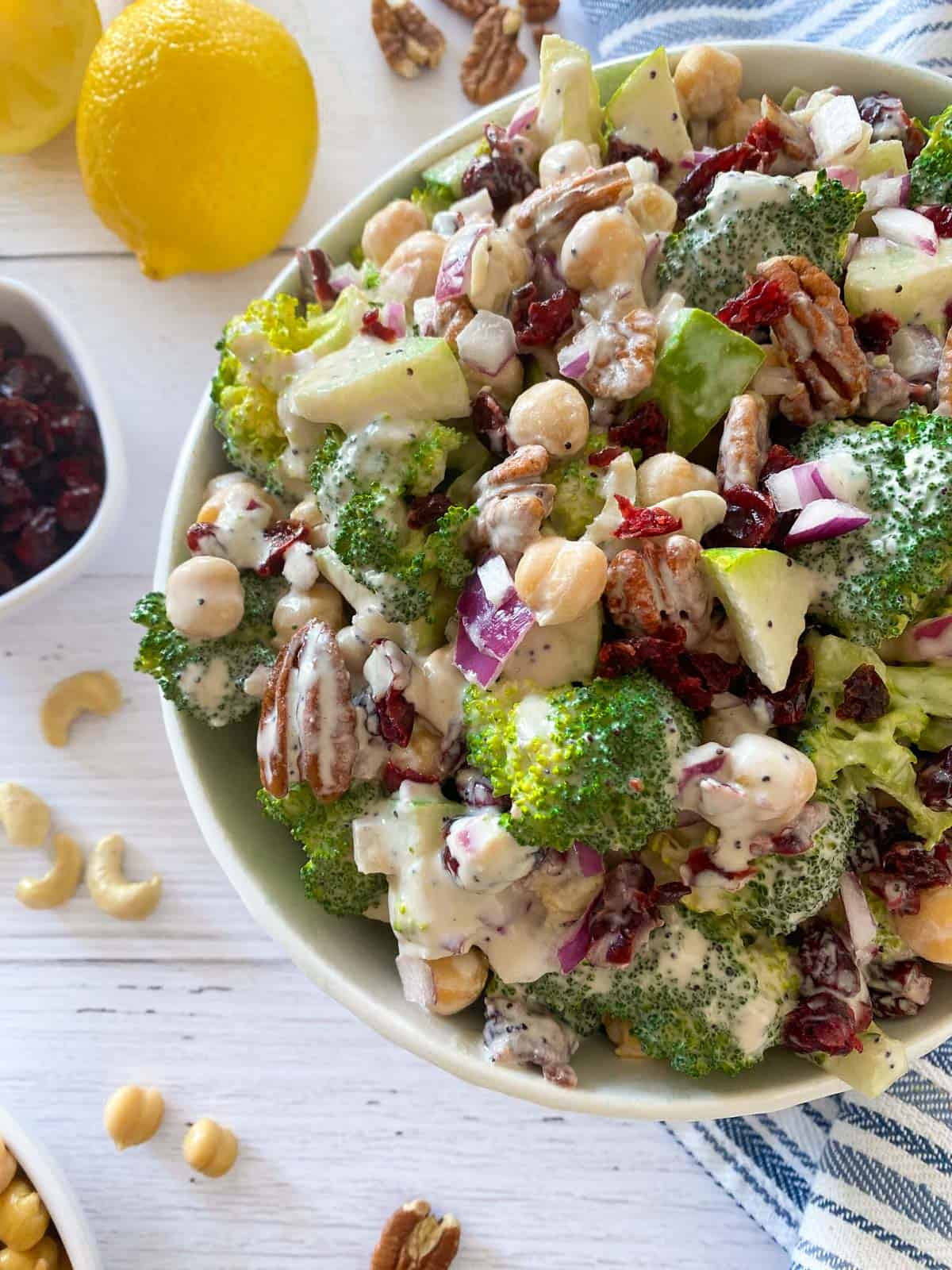 Bowl of broccoli salad with cranberries, pecans, chickpeas, apple and a creamy dressing.