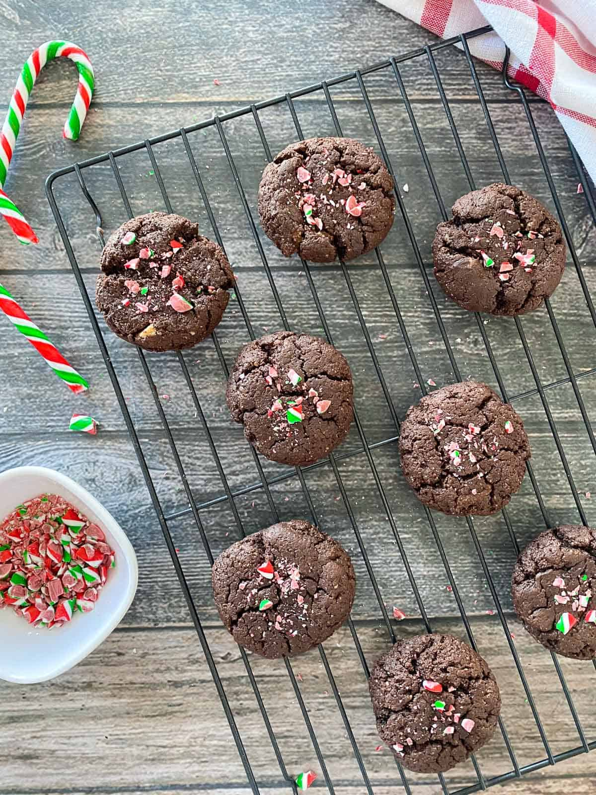Brownie peppermint cookies on cooling rack with crushed candy cane on top.