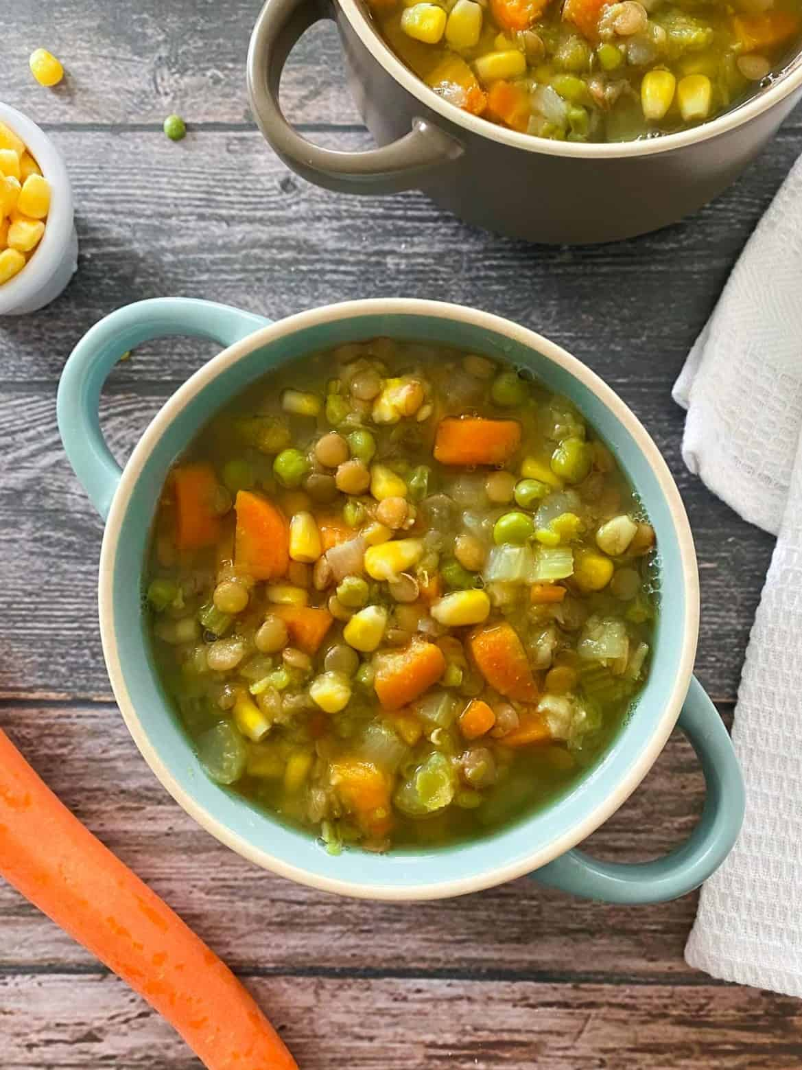 Blue bowl with handles filled with vegetable soup with lentils.