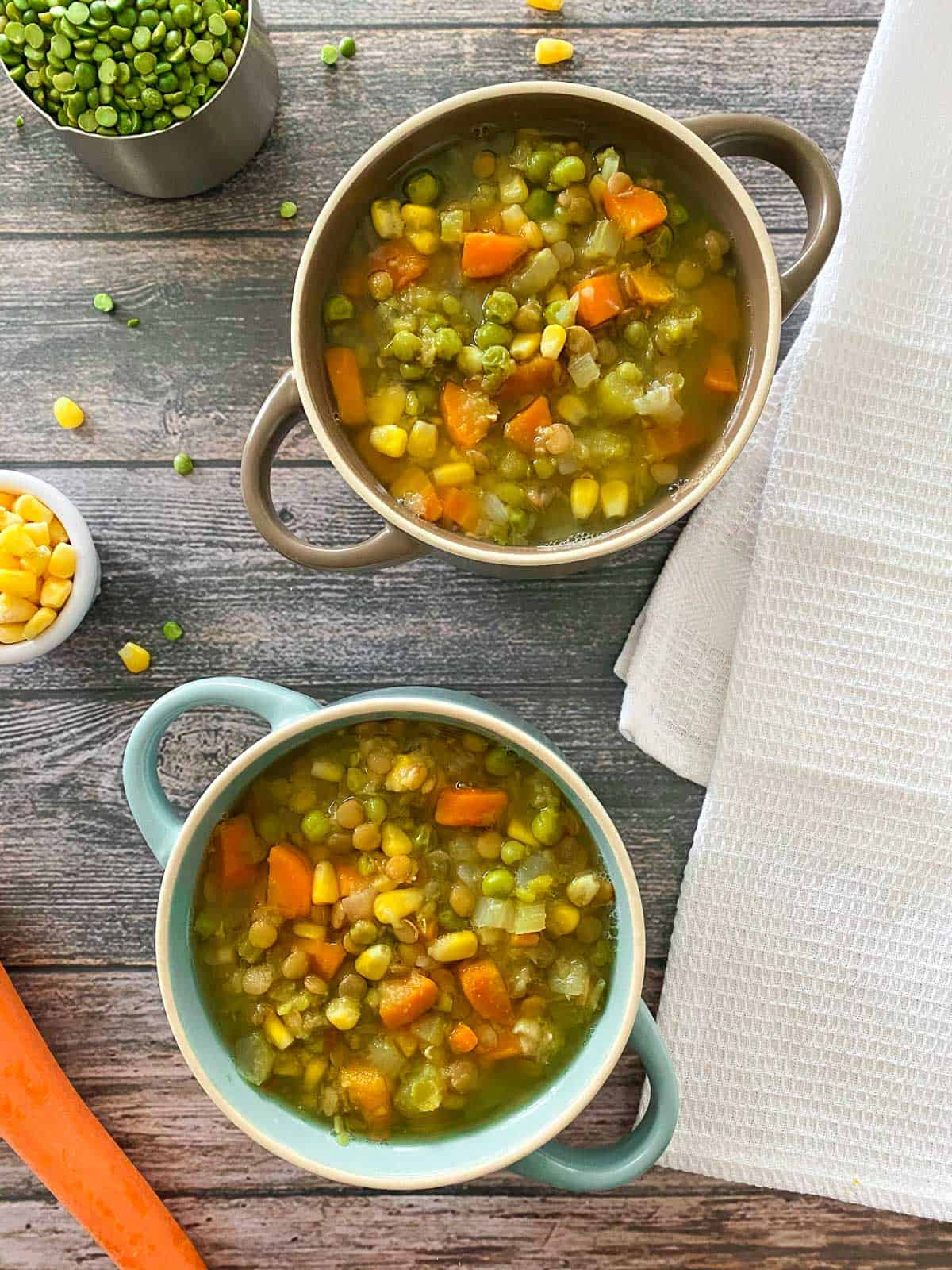 Two bowls of lentil soup with carrots, corn and peas on brown deck.