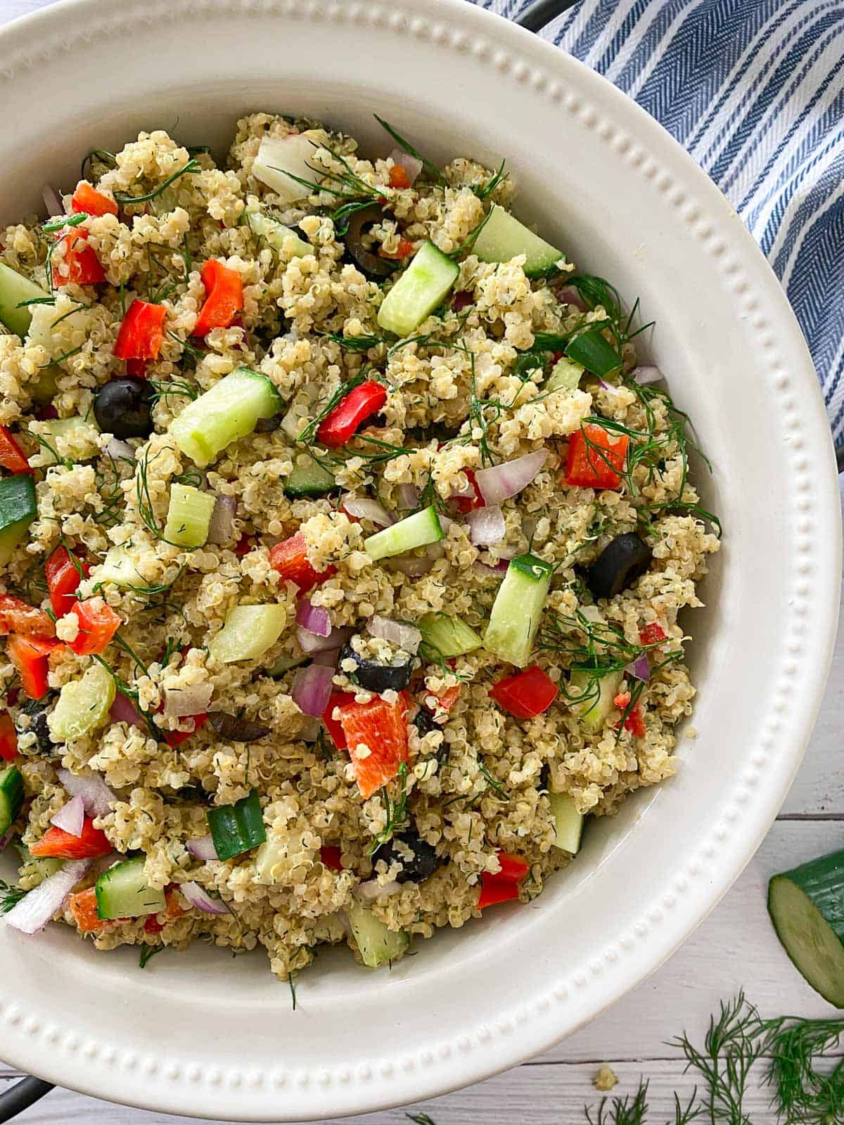 Close up of salad in serving bowl with quinoa, pepper, cucumber, onion, olive and dill.