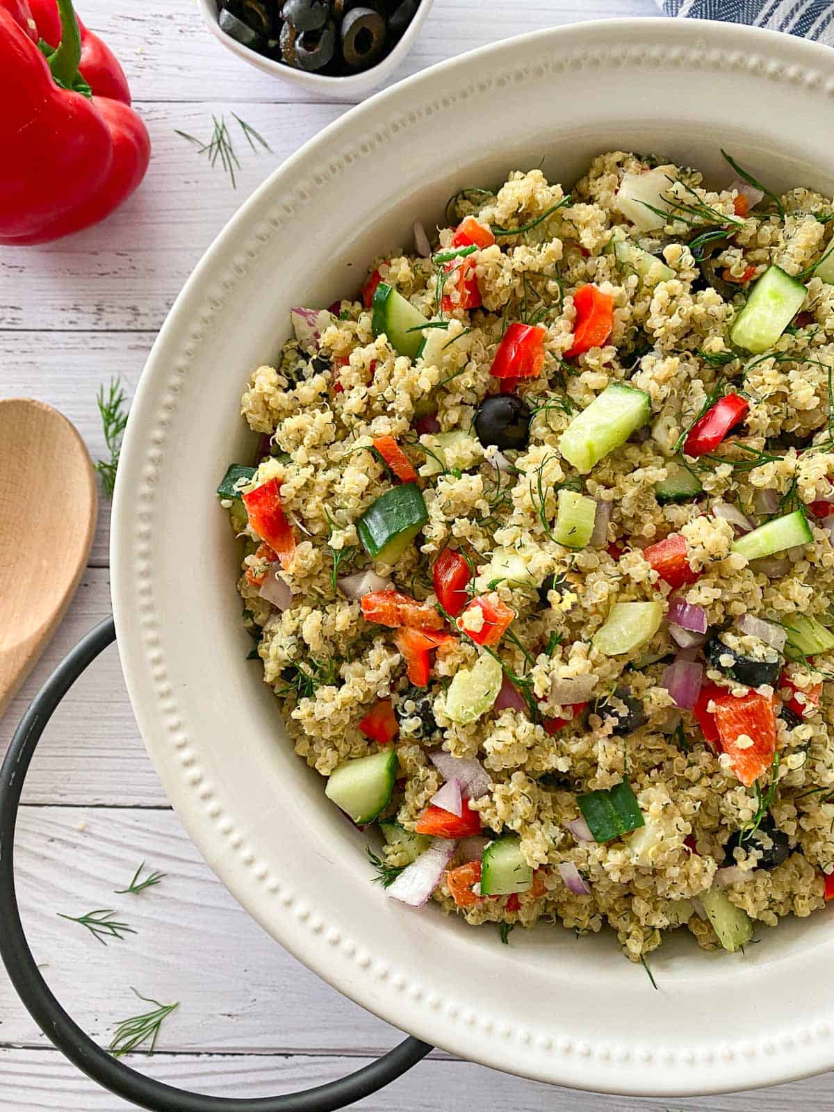 Quinoa pasta salad in large white serving dish with wooden spoon on the side.