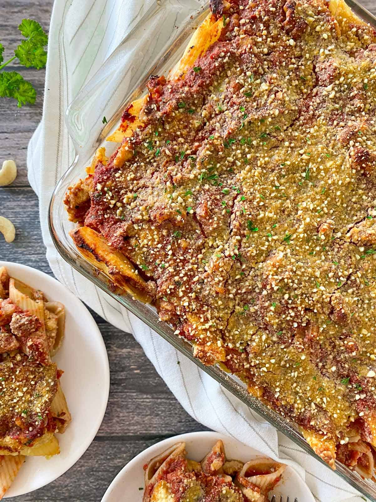 Casserole dish with baked pasta, vegan cheese and parsley sprinkled on top.