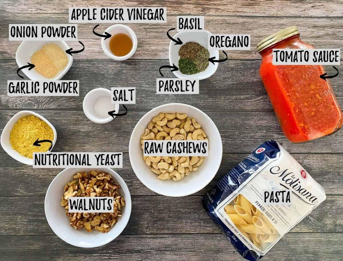 Ingredients to make vegan baked pasta scattered on deck.