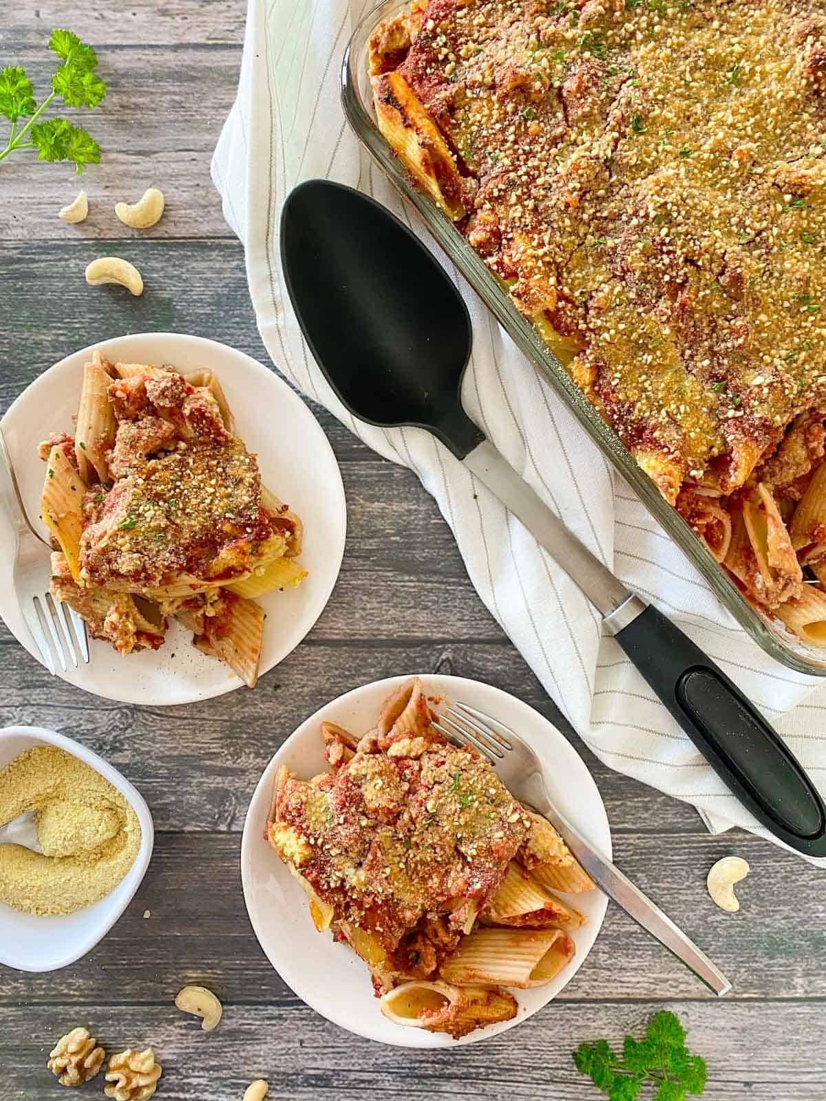 Two plates with baked pasta and the tray of baked pasta beside them.