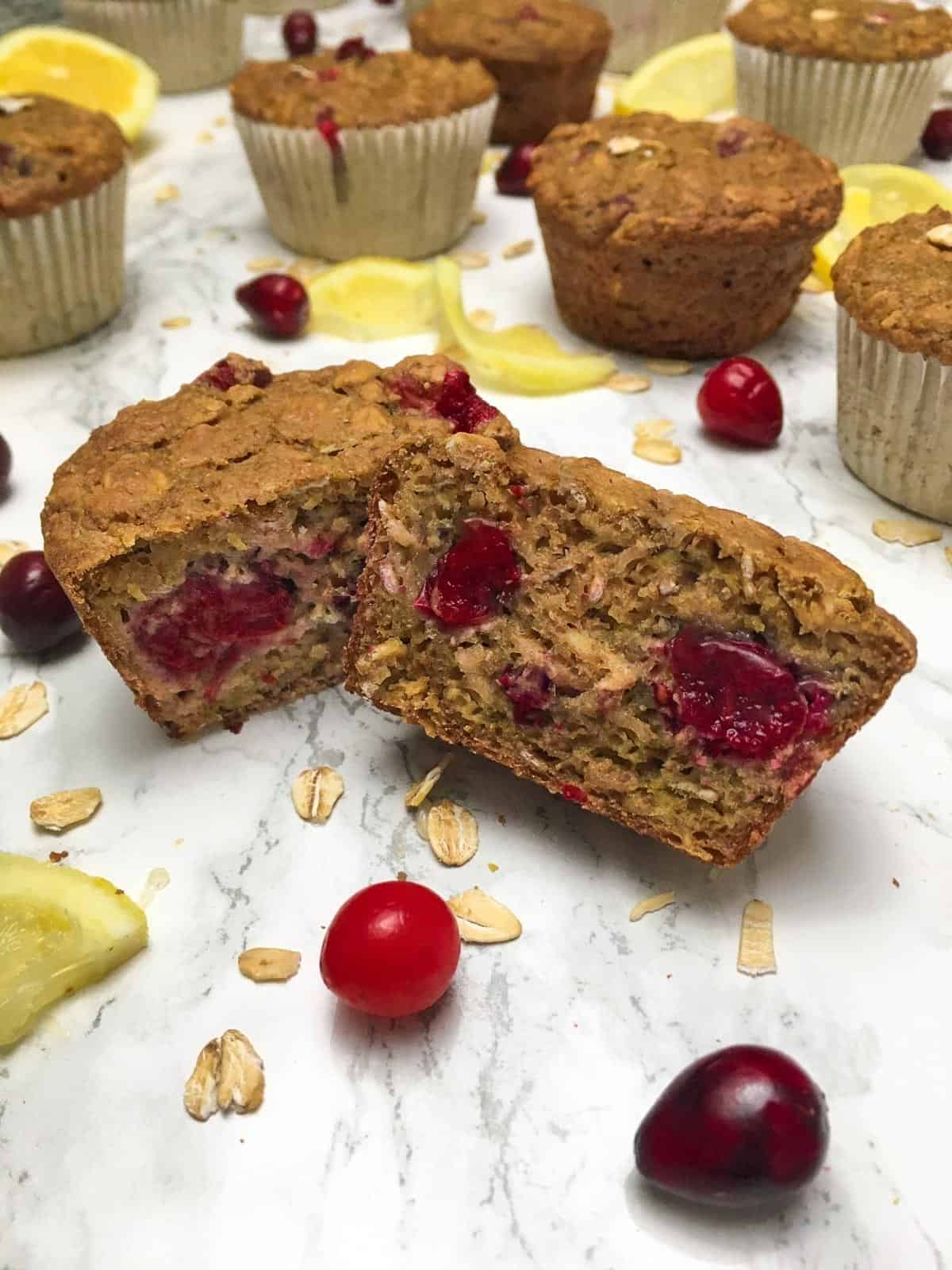 Cranberry muffin sliced in half with more muffins behind.
