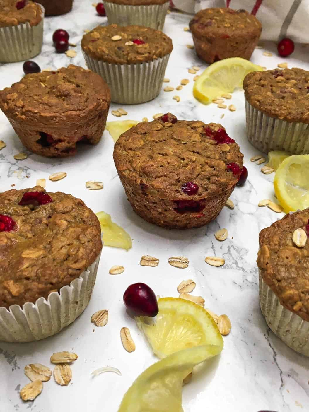Muffins on marble counter with cranberries and lemon slices scattered between them.