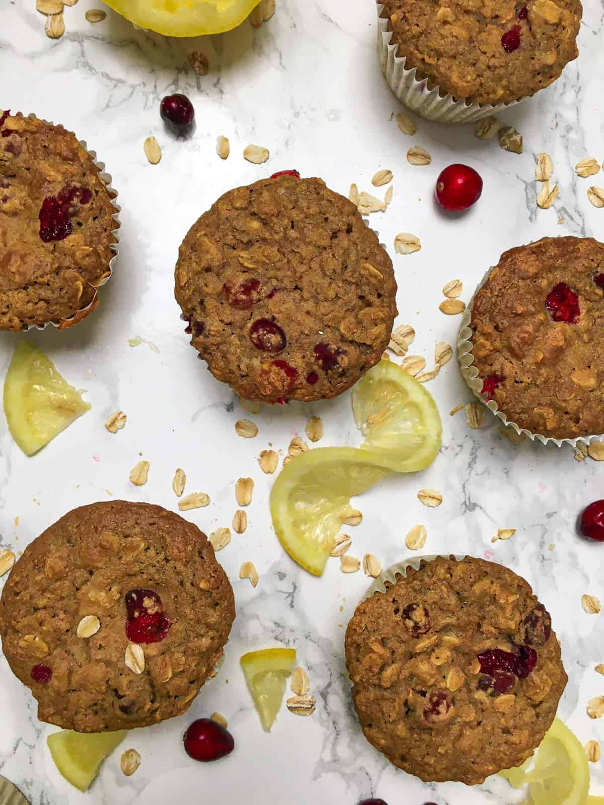 Overhead view of vegan cranberry muffins on marble counter.