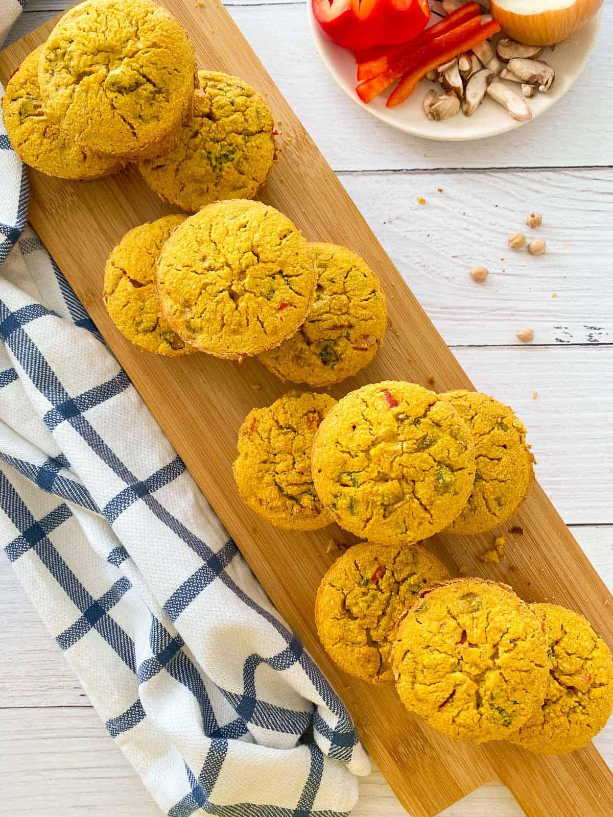 vegan frittata muffins with veggies inside sitting on wooden cutting board.