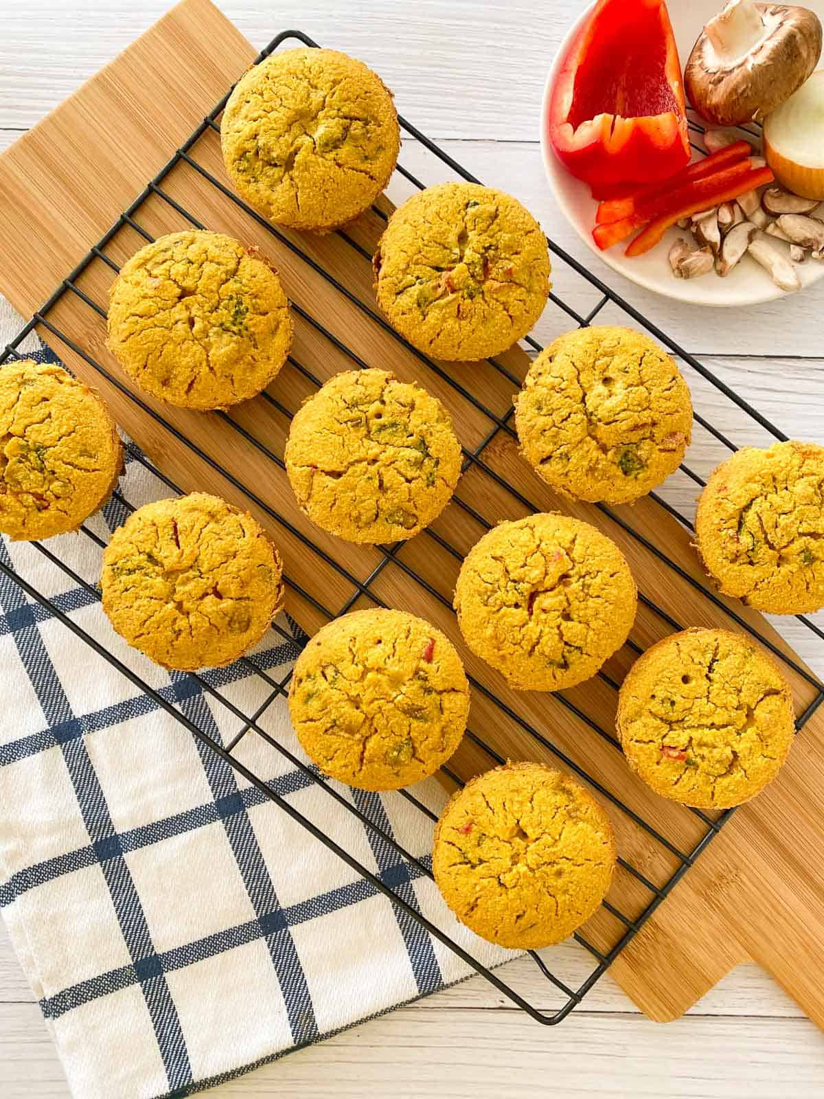 Twelve savoury muffins on cooling rack with cutting board underneath.