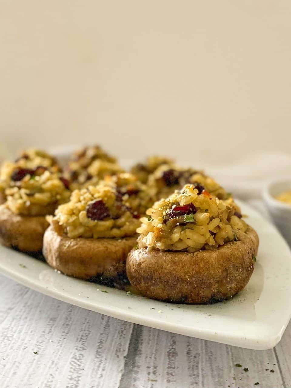 Side view of mushrooms stuffed with risotto and cranberries on white platter.
