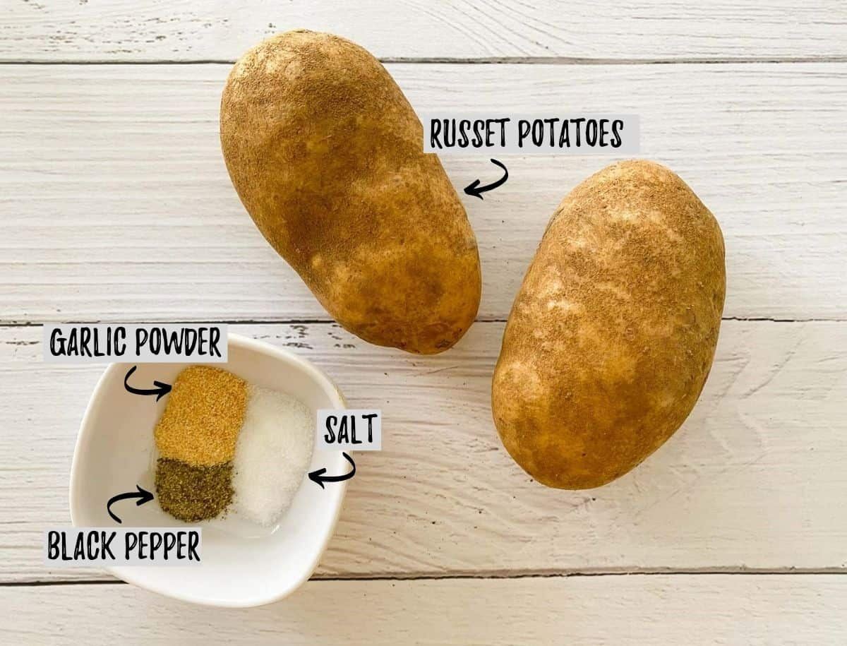 Russet potatoes and a bowl of seasoning on white deck.