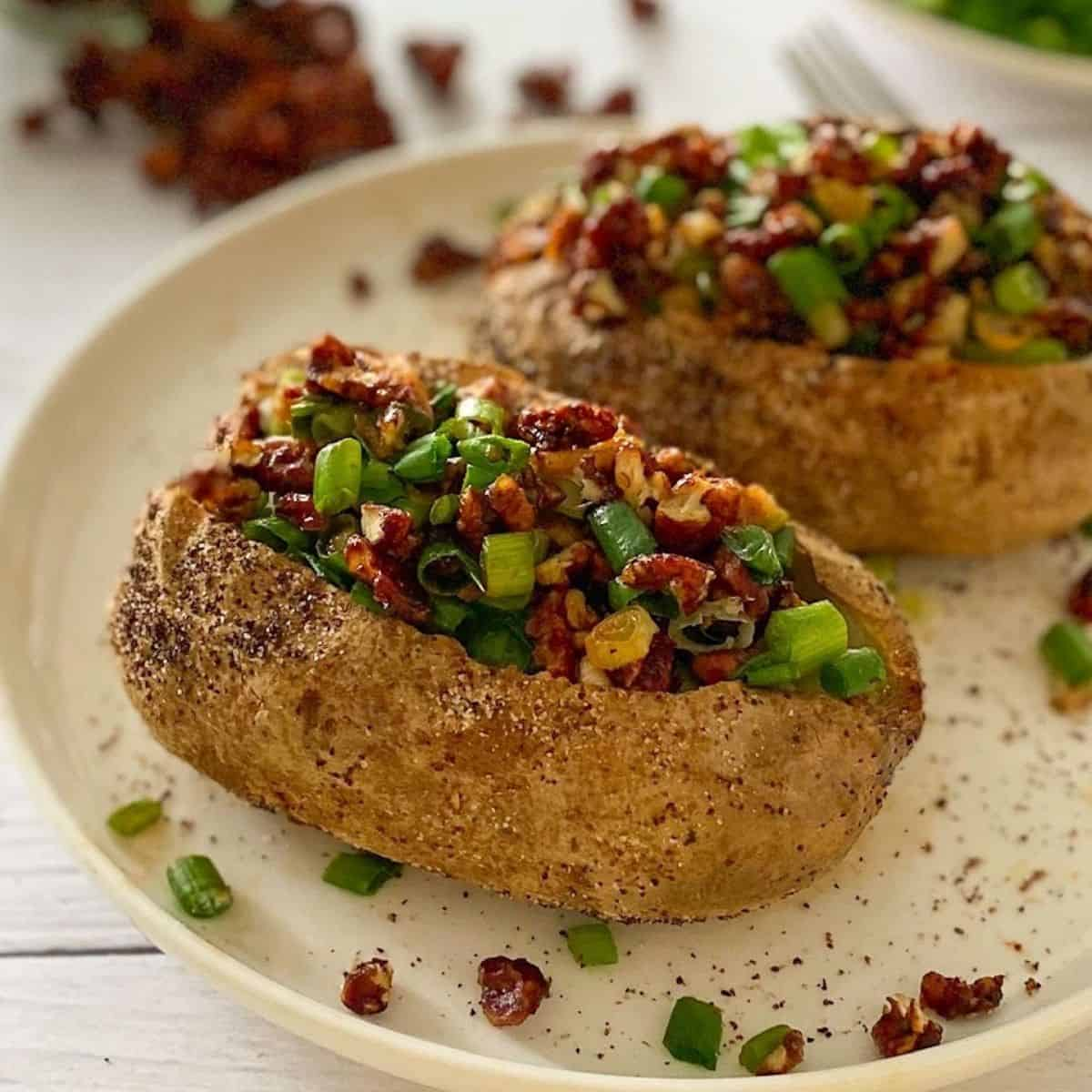 Two baked potatoes in plate, topped with vegan bacon and green onion.