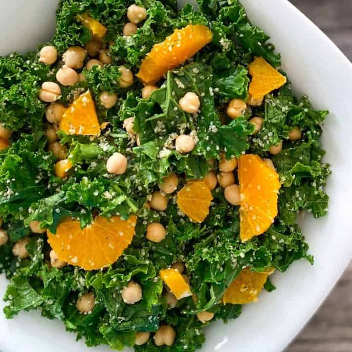 White serving bowl of kale salad with oranges and chickpeas on top.