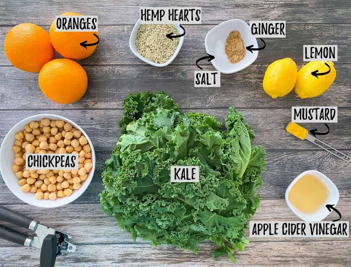 Ingredients to make orange kale salad on brown deck.