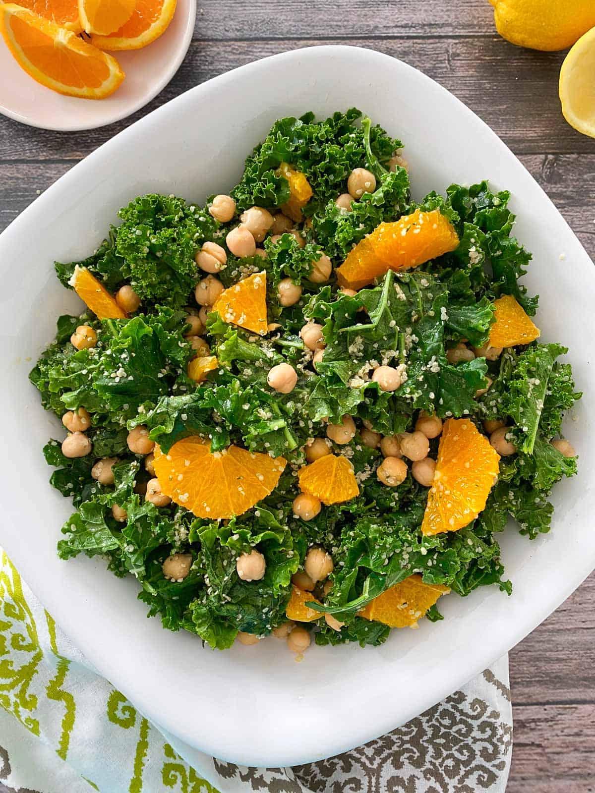 Large white bowl with kale salad, garnished with oranges.