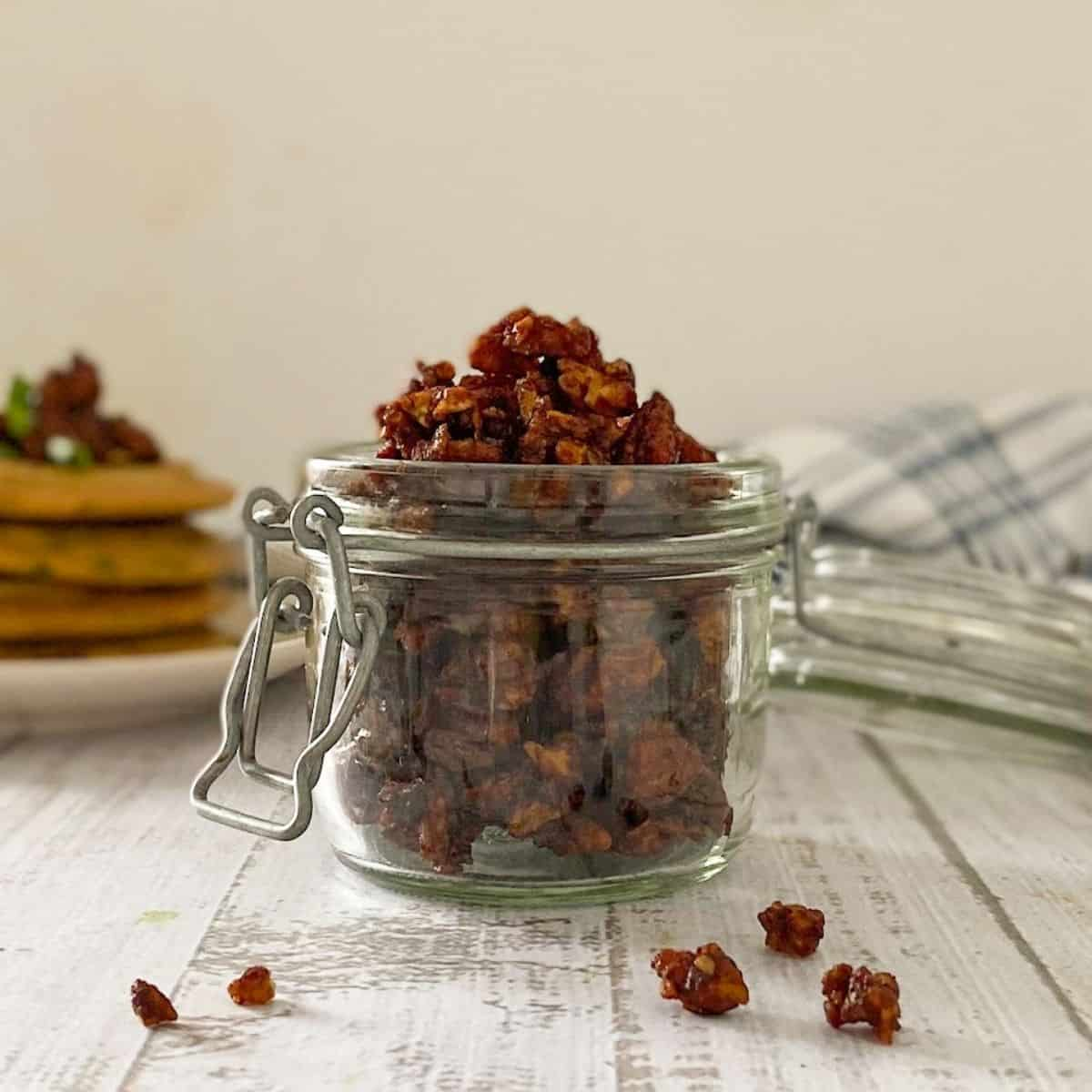 vegan bacon bits in glass jar with pancakes in the background.