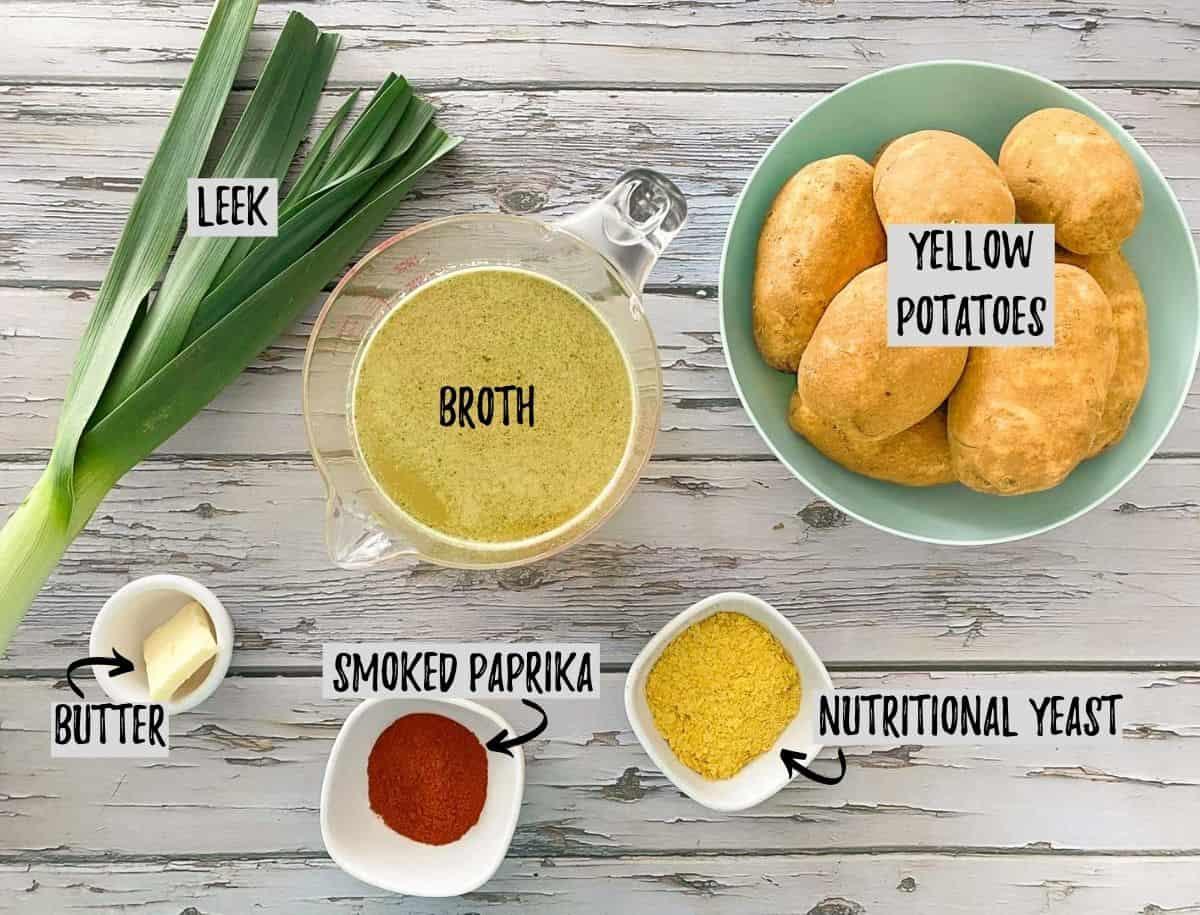 Ingredients to make potato leek soup on grey deck.