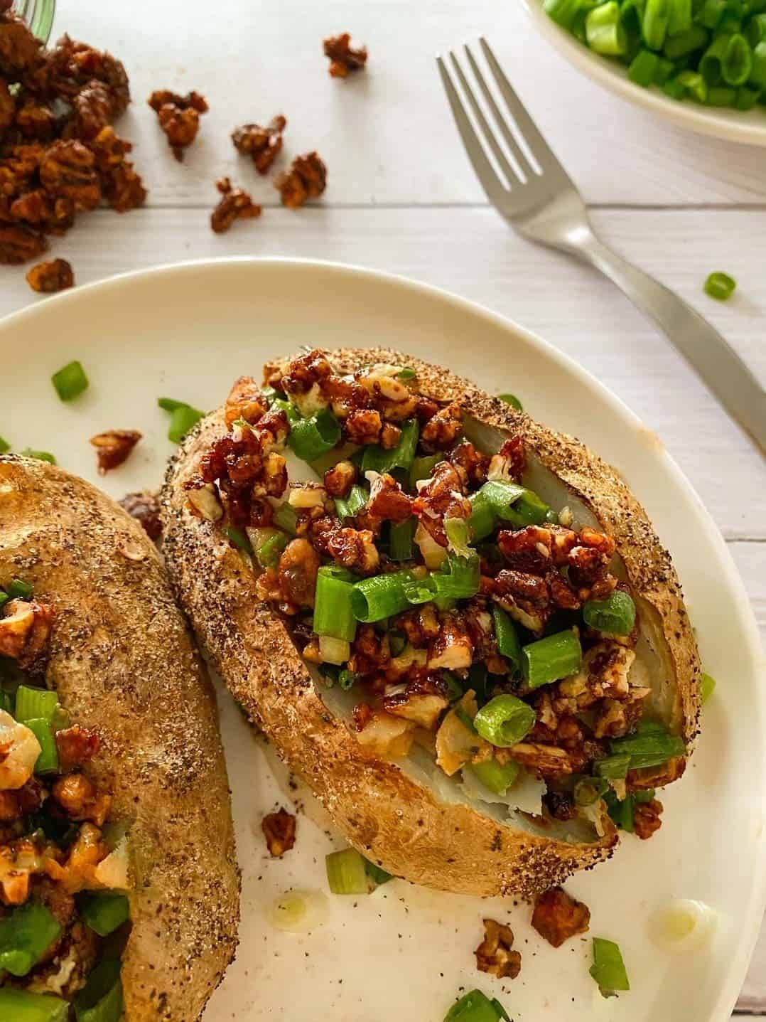 Vegan baked potatoes on white plate with pecan bacon and green onion on top.