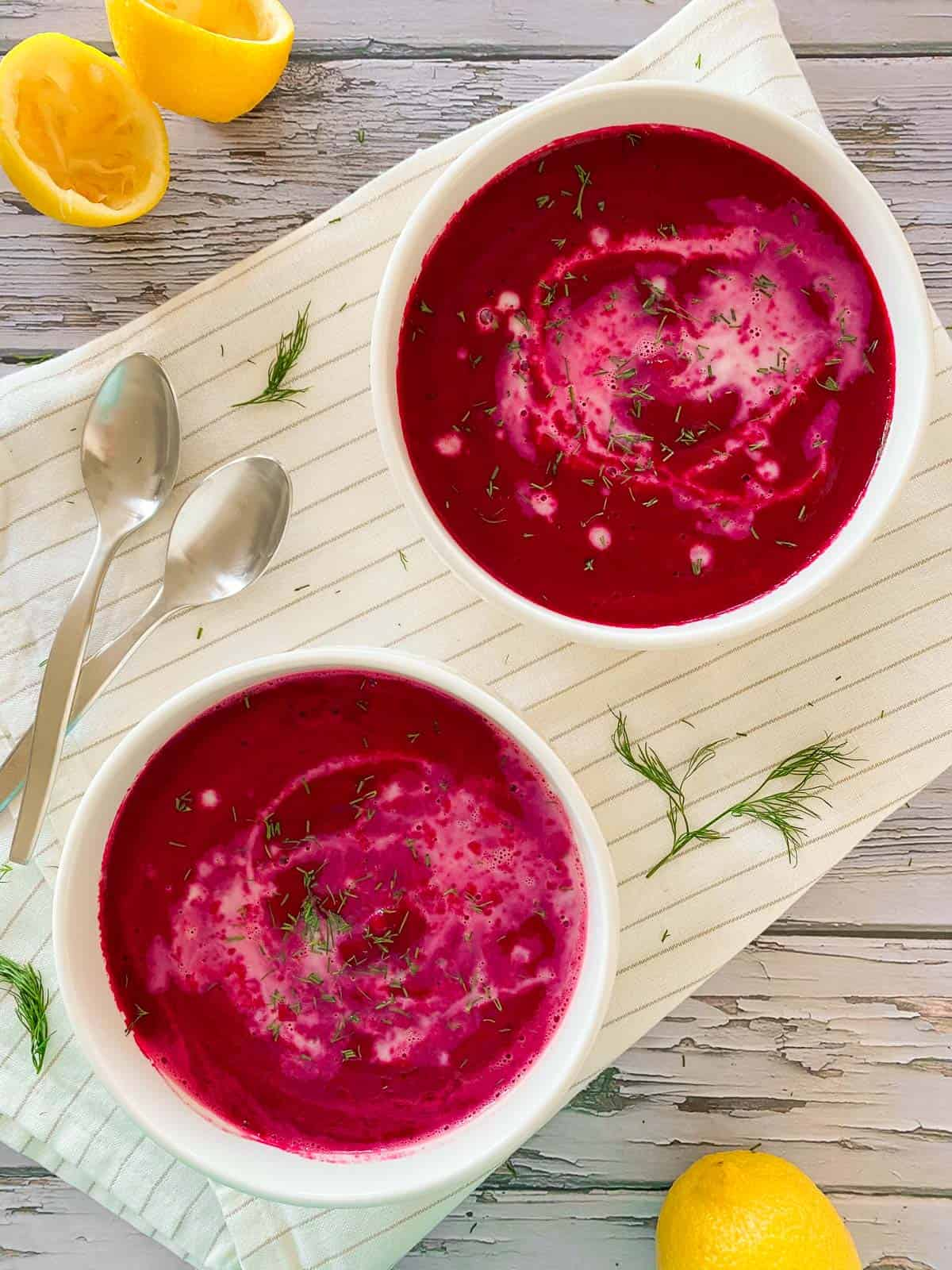 Two bowls filled with beet soup and garnished with cream and dill.