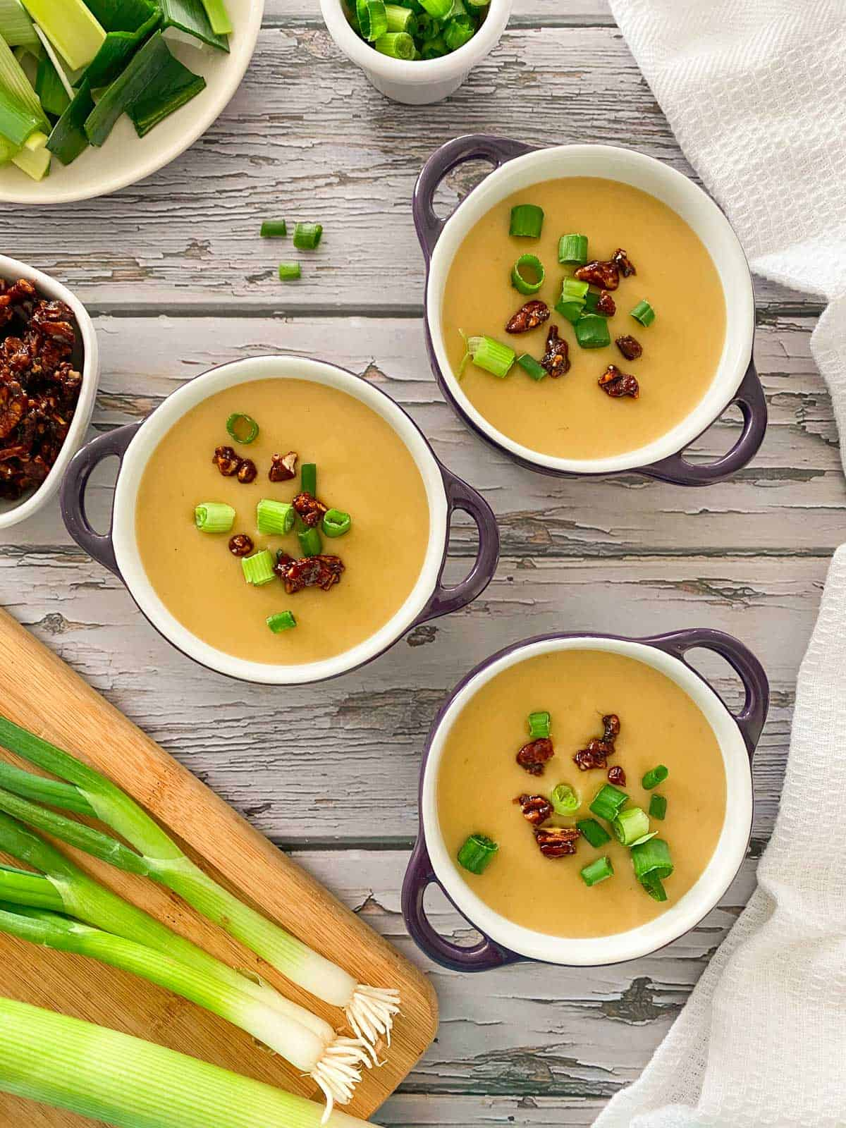Three bowls of soup with bacon and green onion garnish.