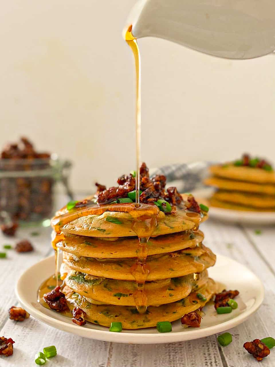 Stack of pancakes with bacon and chives on top and syrup dripping down.