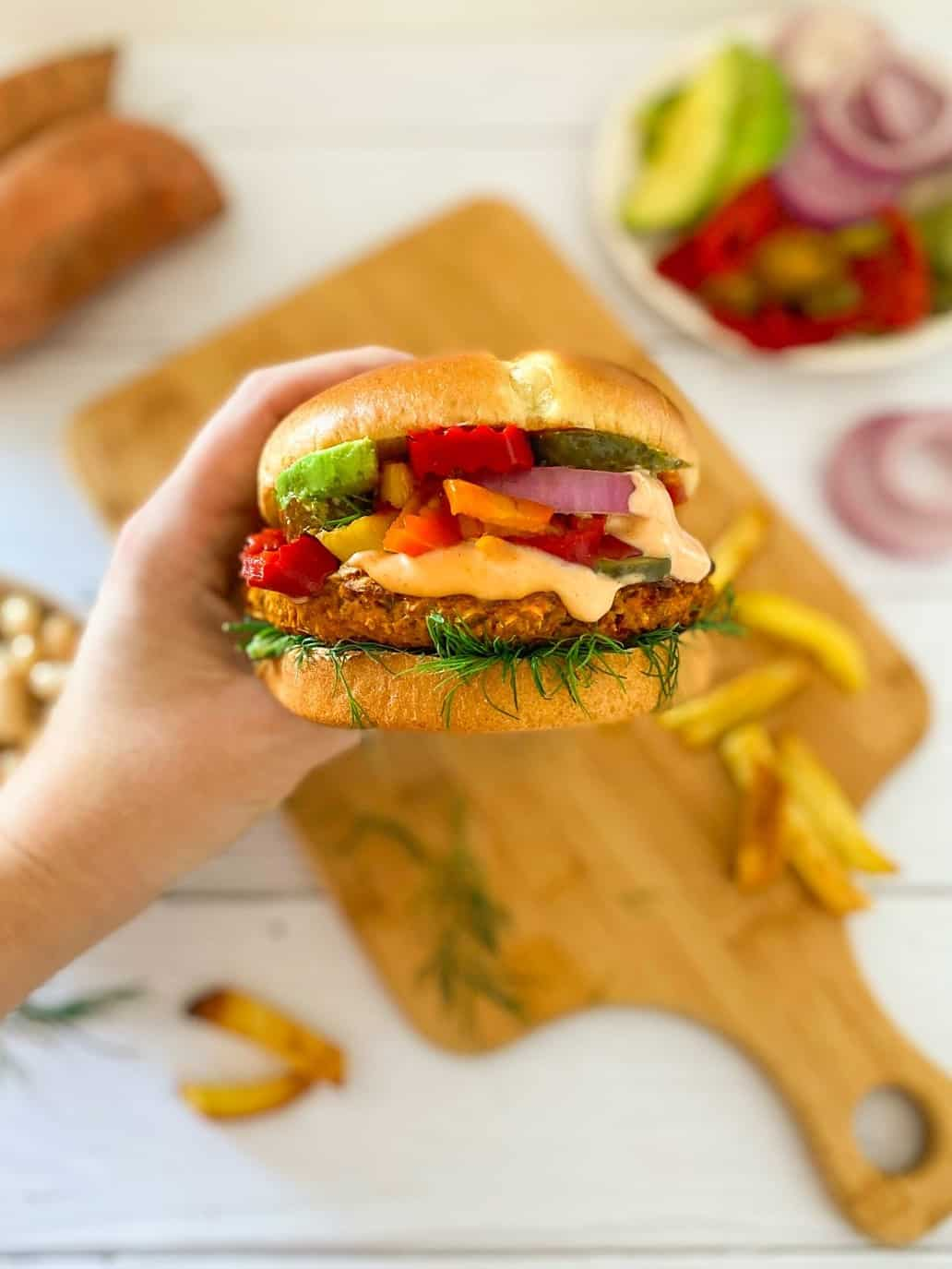 Hand holding vegan sweet potato burger in bun with onion, avocado, peppers and spicy mayo.