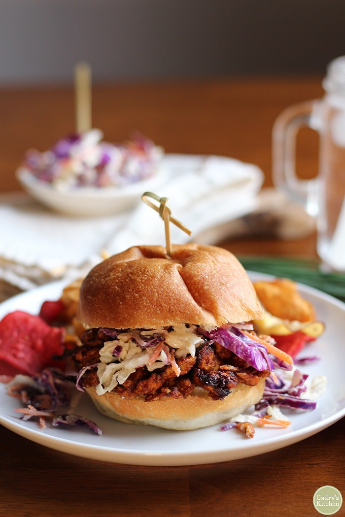 Sandwich with soy curls and coleslaw on white plate.