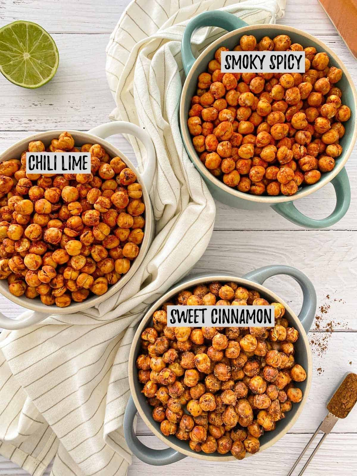 Three flavours of air fried chickpeas in 3 different bowls on white deck.