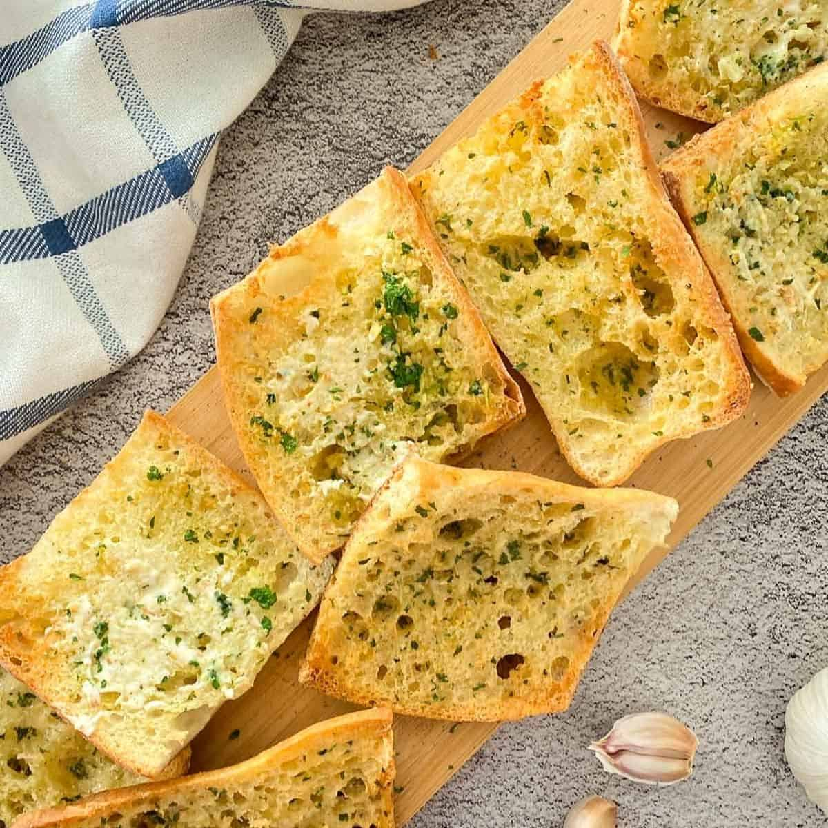 Slices of garlic bread on wooden cutting board.