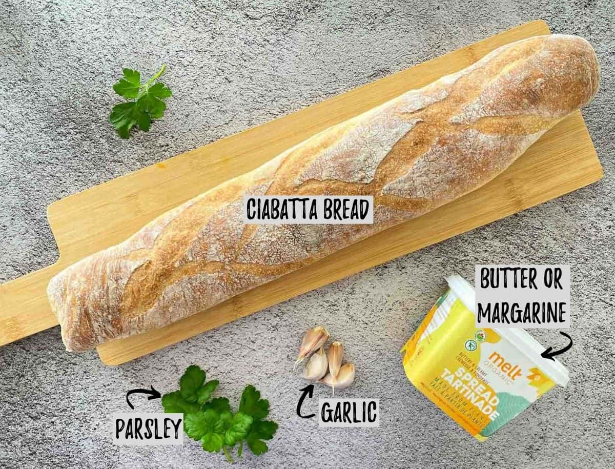 Loaf of bread on cutting board with butter, garlic, and parsley scattered around.