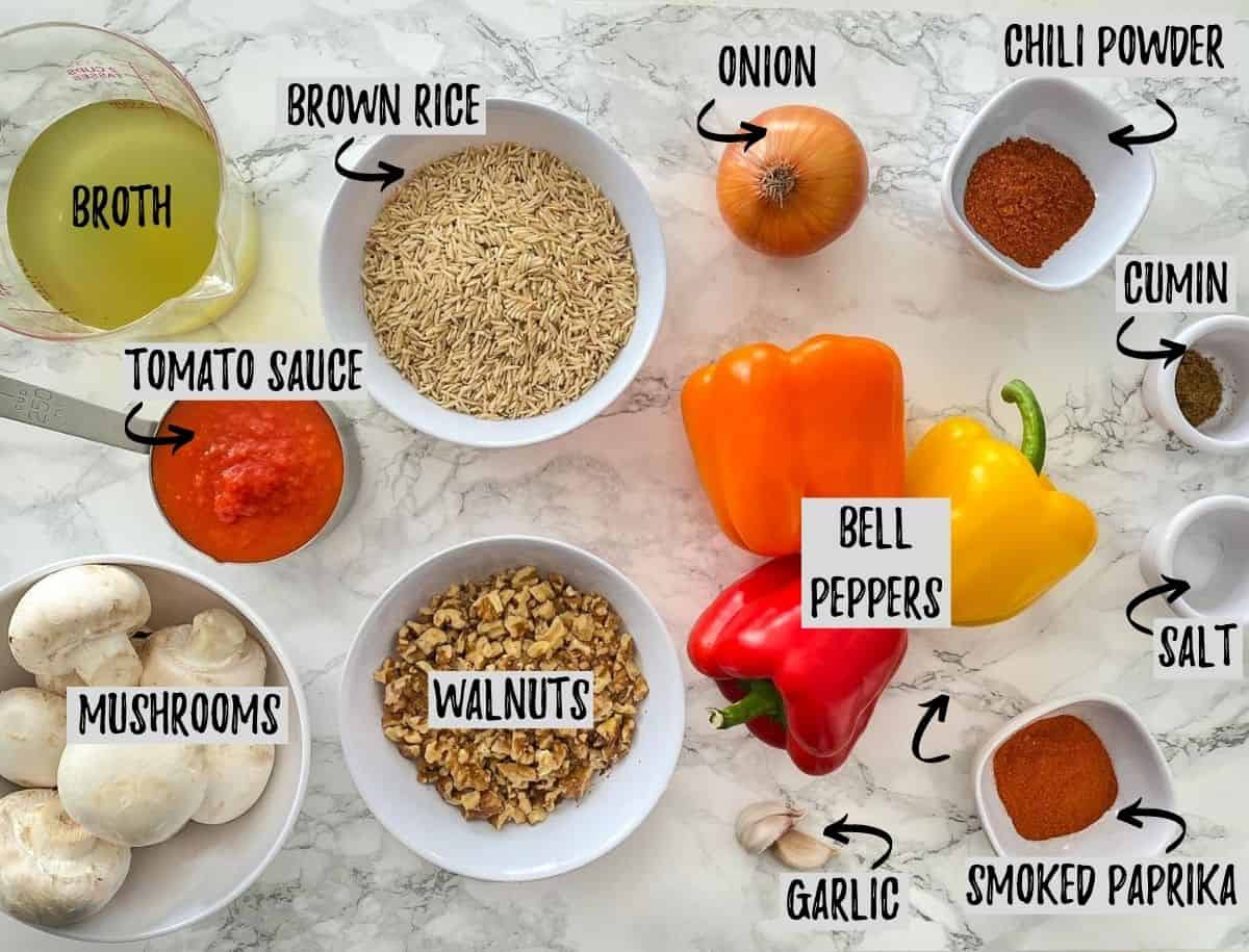 Ingredients needed to make unstuffed peppers scattered on marble counter.