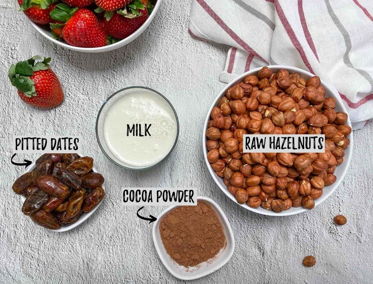 Bowl of hazelnuts, bowl of dates and bowl of cocoa powder and cup of milk.