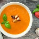 White bowl full of tomato soup with basil and croutons on top.