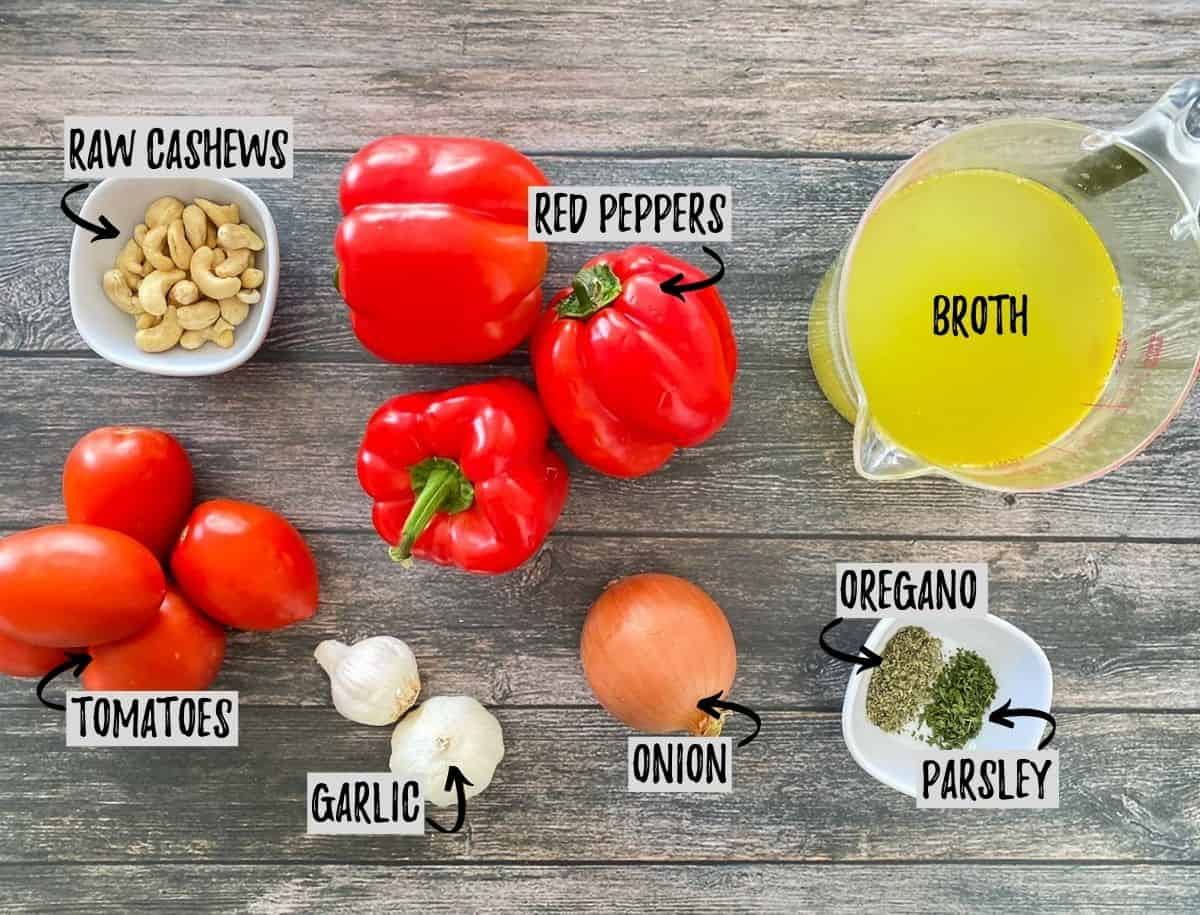 Ingredients needed to make roasted red pepper soup on grey deck.