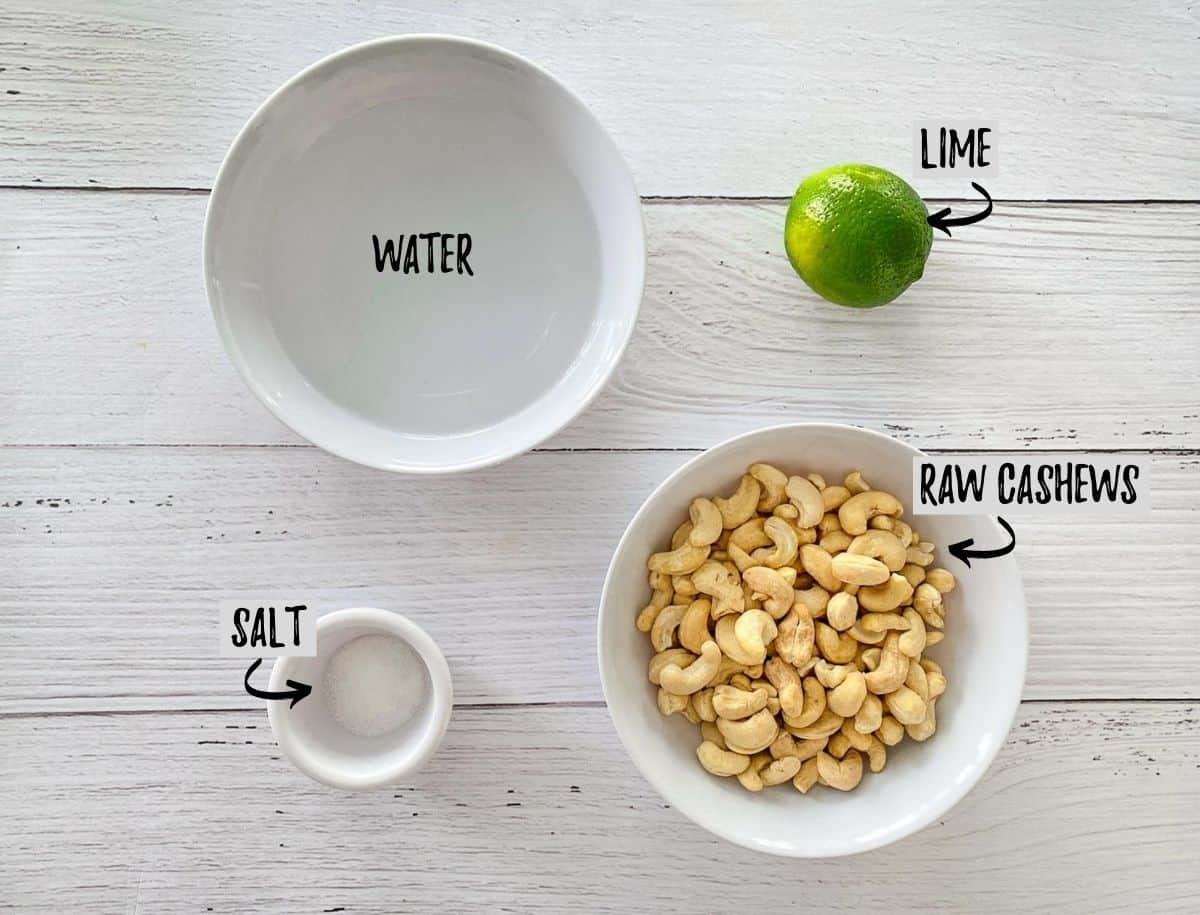 Bowl of water, cashews, salt and a lime on a white deck.